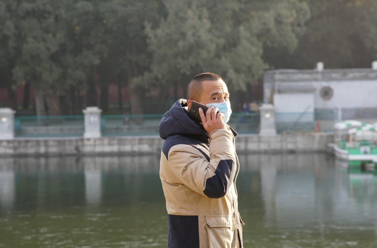 Man talking on cell phone with mask