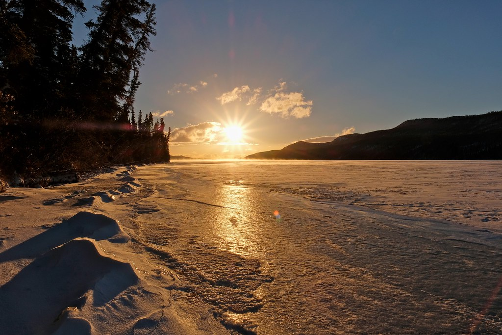 Setting sun on iced over lake