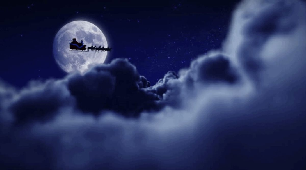 santa flying in front of night moon