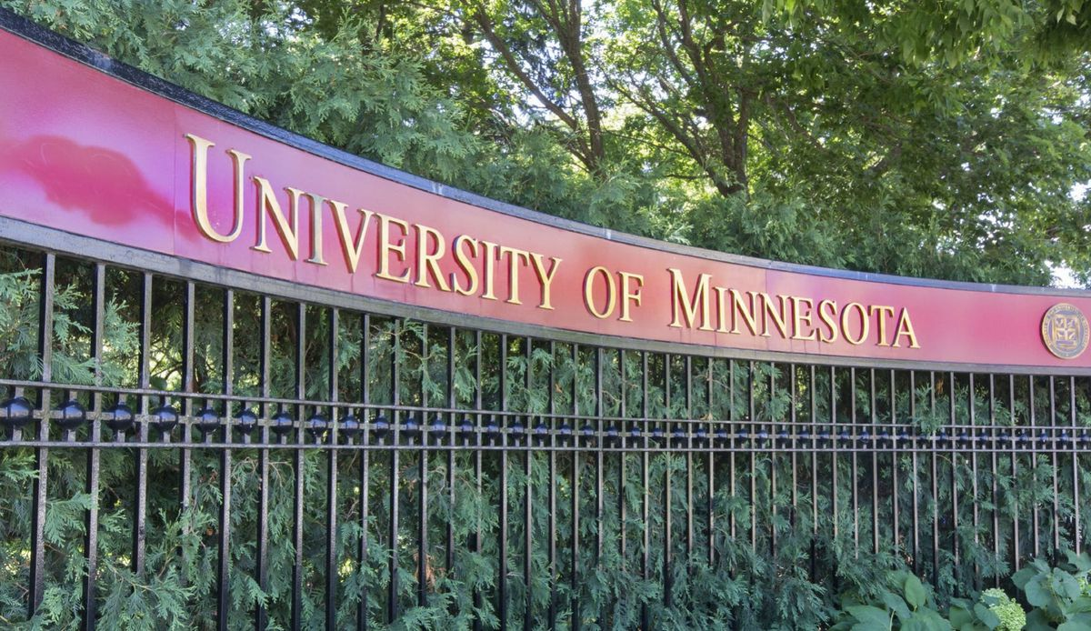 Entrance gate for University of Minnesota, with a red sign and gold lettering.